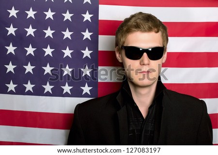 Young man in sunglasses on a background of the American flag