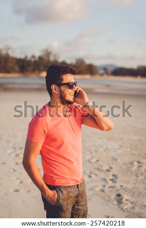 young man in sunglasses on the phone at the beach - stock photo