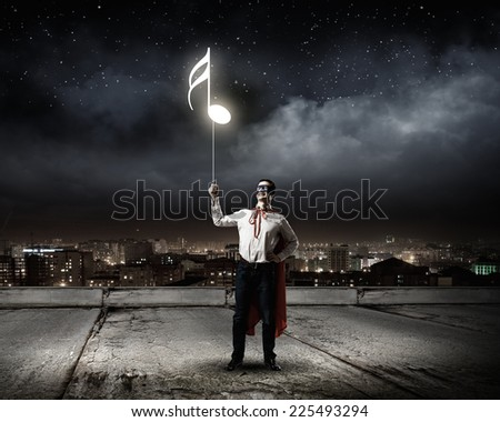 Young man in superhero costume holding balloon in hand - stock photo