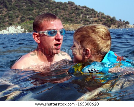 young man in swimming glasses swim to the little boy in inflatable lifejacket