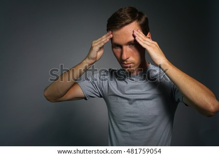 Young man in t-shirt thinking or experiencing headaches.