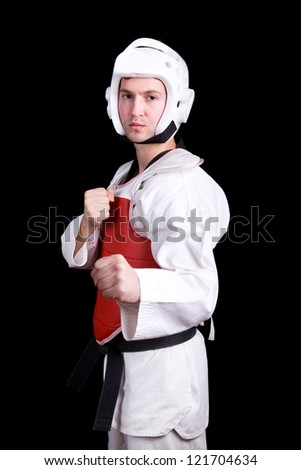Young man in Taekwondo gear standing against black background - stock photo