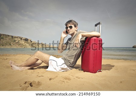 young man in the beach with a suitcase - stock photo