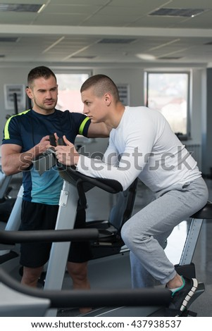 Young Man In The Gym with Personal Trainer - Exercising His Legs Doing Cardio Training On Bicycle
