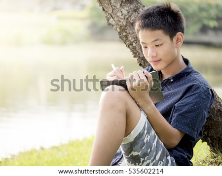 young man in the park sitting on the grass, enthusiastically writing with a book