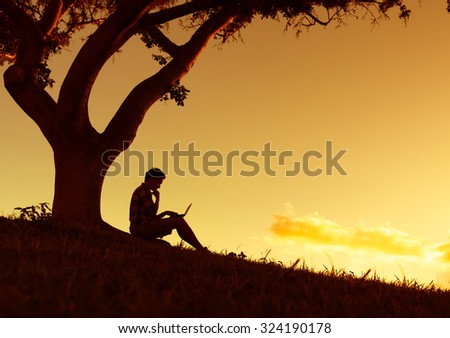 Young man in the park working on his computer. - stock photo