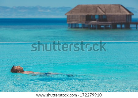 Young man in the pool and ocean in the background. Maldives - stock photo