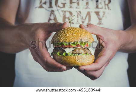 Young man in the white t-shirt holding in hands fast food burger, american meal on a black background.