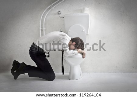 Young man in tie puts his head in a toilet - stock photo