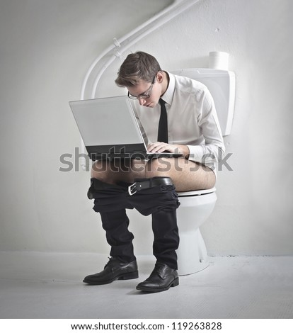 Young man in tie using a laptop computer on a toilet - stock photo
