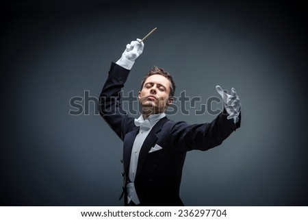 Young man in tuxedo conducting - stock photo