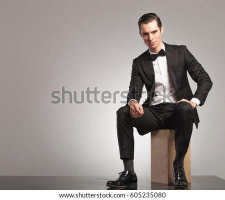 young man in tuxedo is sitting with open coat on grey studio background