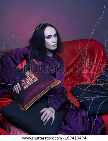 Young man in violet chinese costume sitting on the sofa