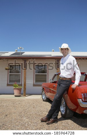 Young man in Western style attire leaning on convertible - stock photo