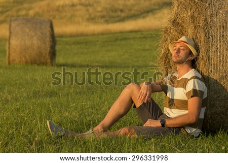 Young man in wheat field leaning on haystack