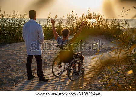 Young man in wheelchair and his doctor relaxing on the beach over sunset. - stock photo