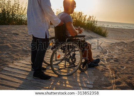 Young man in wheelchair and his doctor relaxing on the road to the beach. - stock photo
