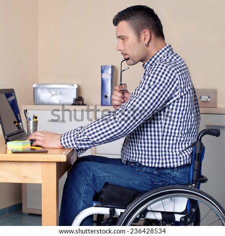 young man in wheelchair in office is using his laptop, disabled young man is surfing in internet  - stock photo
