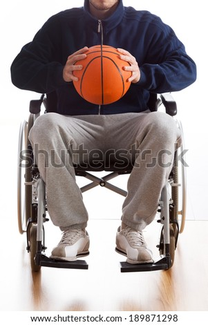 Young man in wheelchair with basketball, vertical - stock photo