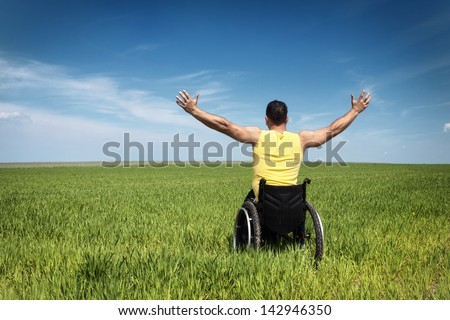 young man in wheelchair with wide opened arms enjoying his life - stock photo