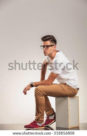 young man in white shirt looking away while seated on a box  - stock photo