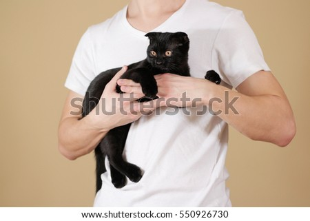 Young man in white t shirt holding a black Scottish fold cat. On an isolated background.