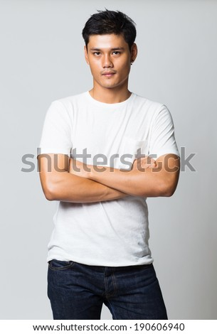 Young man in white t-shirt, with arms crossed isolated on white background