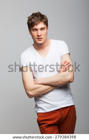 young man in white tshirt with folded arms on gray background - stock photo