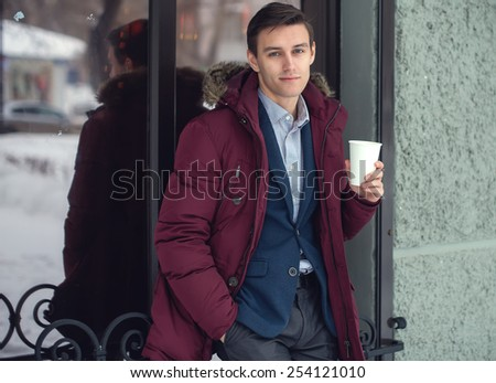 Young man in winter coat woth coffee to go standing against the cafe wall. - stock photo