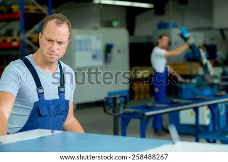 young man in workwear is  busy in factory