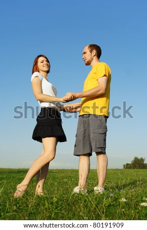 young man in yellow shirt and redhead girl standing on summer lawn and holding for hands, full body
