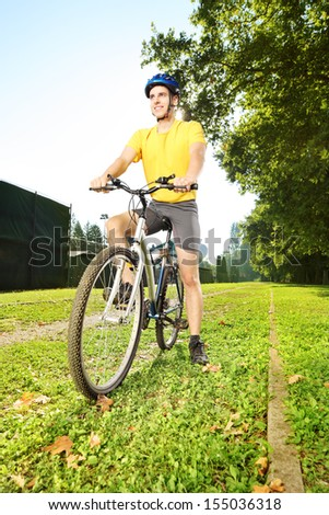Young man in yellow shirt standing on a mountain bike in a park - stock photo