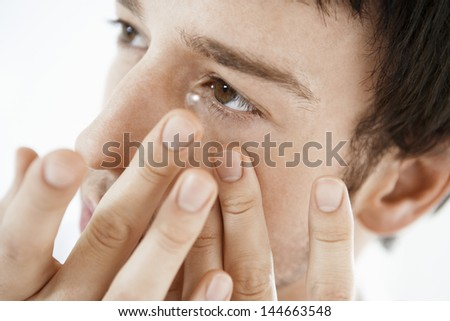 Young man inserting a contact lens isolated on white background - stock photo