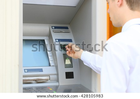 young man inserting a credit card to ATM