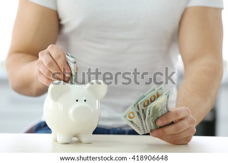 Young man inserting money in a piggy bank on wooden table.