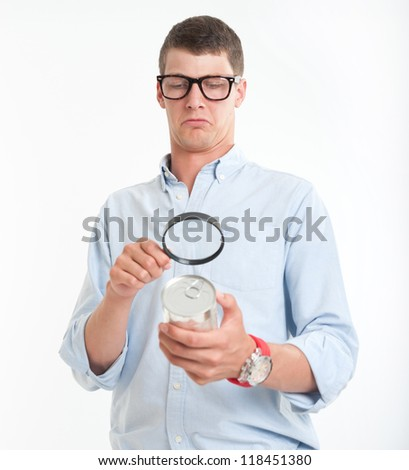 Young man inspecting a cans nutrition label with a magnifying glass - stock photo