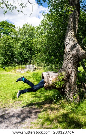 Young man is being eaten by a big tree. Trees and a path visible in the background - stock photo