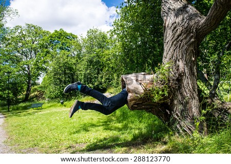 Young man is being eaten by a big tree. Trees and a path visible in the background. - stock photo