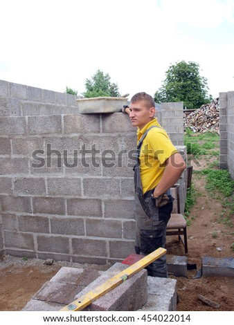 Young man is building house walls from concrete blocks.
