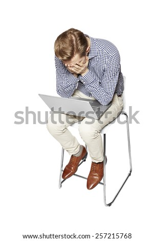 Young man is crying over the keyboard. Isolated on white background. - stock photo