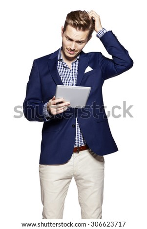 Young man is gesturing and reading from digital tablet. Isolated on white background.