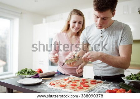 Young man is grating cheese on the pizza. Young couple preparing the pizza in the kitchen. Young man and blond hair woman relaxing and having fun with cooking. - stock photo