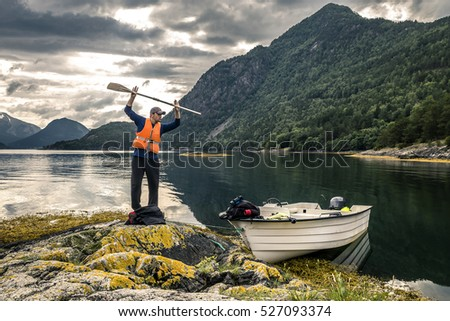 Young man is having fun with paddle near by boat, Norway