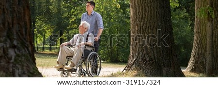 Young man is helping his grandfather in the park - stock photo