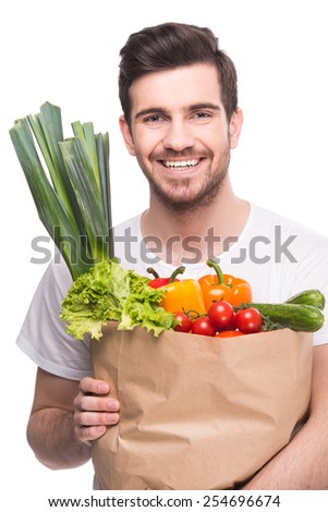 Young man is holding a bag full of vegetables, on white background. - stock photo