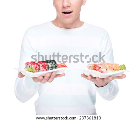 Young man is holding a plate with sushi, isolated against white background. - stock photo