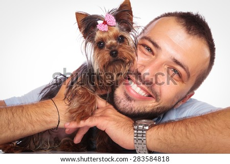 young man is holding his pet yorkshire terrier puppy dog and smiles to the camera - stock photo