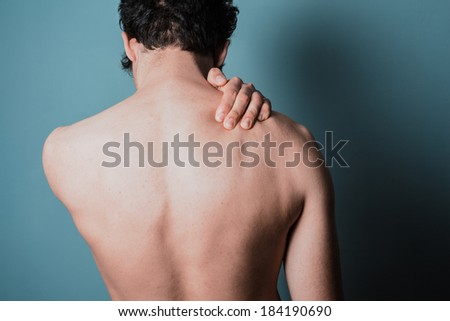 Young man is in pain and is massaging his sore neck - stock photo