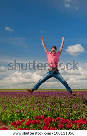 Young man is jumping above the typical dutch tulips - stock photo