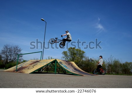 Young man is jumping on his bmx. His friend is looking at it. - stock photo